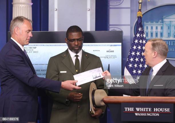 White House press secretary Sean Spicer gives Interior Secretary Ryan Zinke the first quarter check of US President Donald Trump's salary which he...