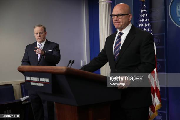 White House Press Secretary Sean Spicer points to a reporter as National security advisor HR McMaster prepares to speak during a press briefing in...