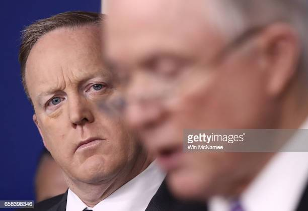 White House press secretary Sean Spicer watches as US Attorney General Jeff Sessions delivers remarks during the daily White House press briefing...