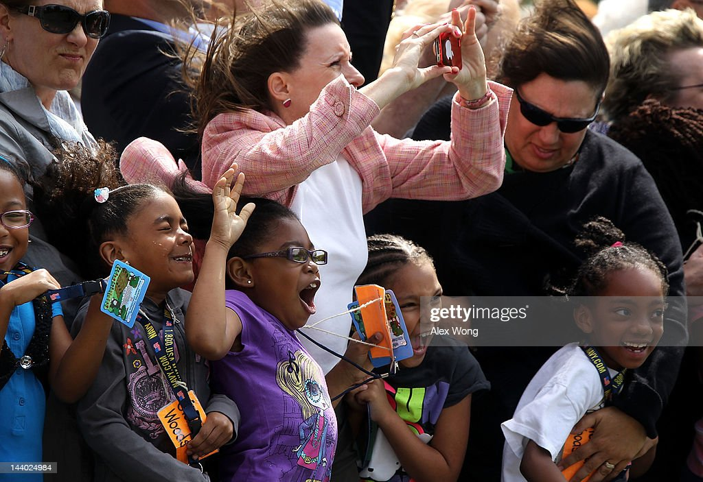 White House visitors react to the rotor wash as Marine One with US President Barack Obama aboard takes off from the White House May 8 2012 in...