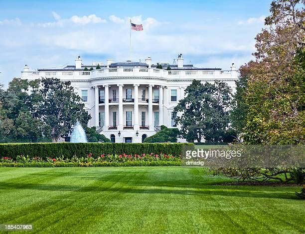 Maison blanche avec la Fontaine, fleurs et la pelouse verdoyante