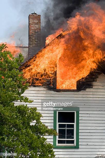 White House with green trim attic is on fire