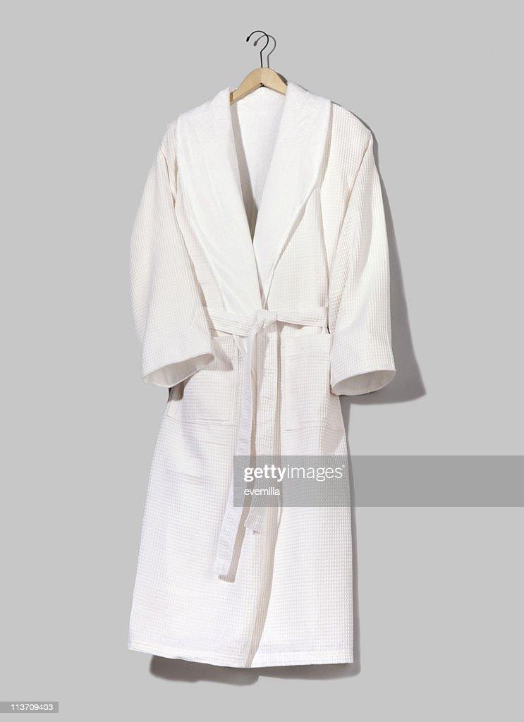 A white hung up bathrobe on a grey wall