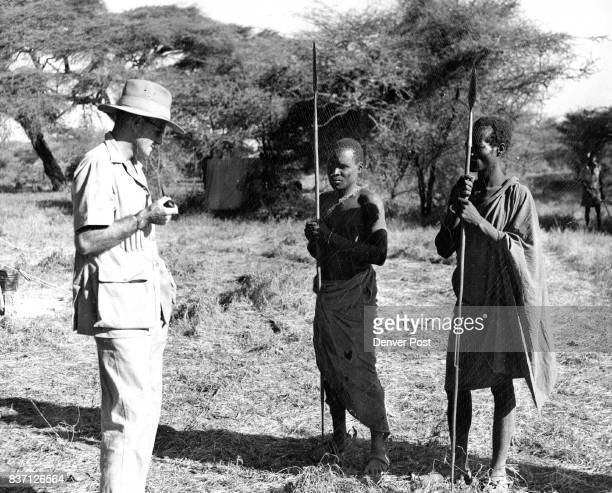 White hunter or guide Frank Bowman issues directions in Swahili to the two native Turkana trackers key men in any African safari The natives carry...
