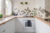 White hygge kitchen with hexagonal tiles, wooden countertop and simple cupboards