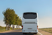White intercity bus is driving along the road. Back view. Sunny day. The sky without clouds.