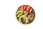White isolated background with clipping paths muesli or granola on white bowl top with fresh blueberries, strawberries and avocado for breakfast in top view flat lay. Healthy food concept.