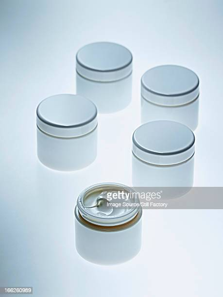 White jars of lotion on counter