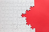White jigsaw puzzle on a red background