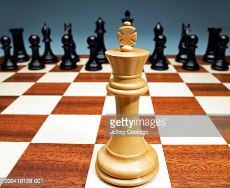 White king facing black chess pieces (wide angle) : Stock Photo