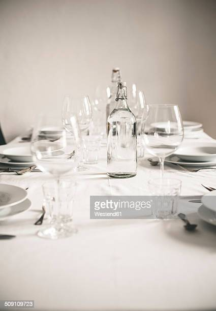 White laid table with glasses and water bottles