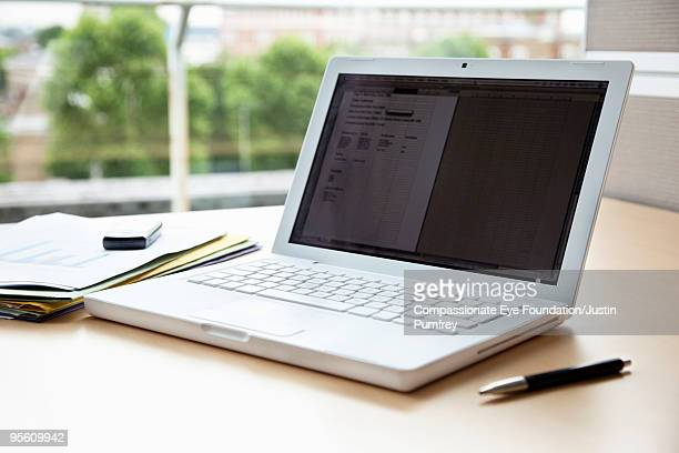 White laptop computer sitting on desk with papers