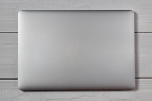 White closed laptop on wooden table background. Stiduo shot.