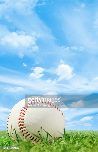 White leather baseball on grass pitch with blue sky