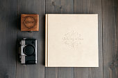 White leather wedding album, wooden box with inscription Wedding day and vintage photo camera. On wooden background