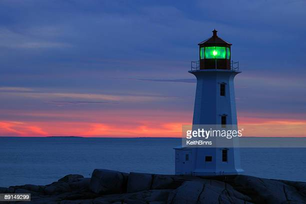 White lighthouse with green lantern at dusk