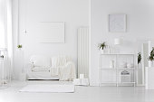 Minimal, white living room interior with couch, shelves, posters and rug