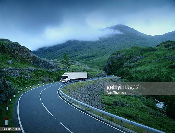 White lorry on road through rural landscape (Digital Composite)