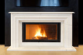 white, marble fireplace and burning fire