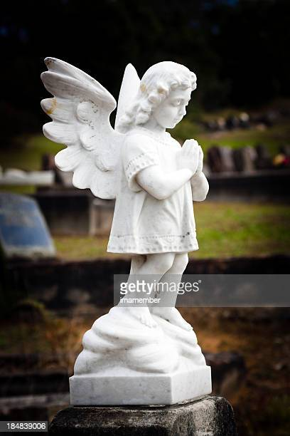 White marble statue of praying little angel in cemetery, vignette