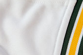 Full frame image of white material and a seam that connects a green and yellow band.  The material is a part of a team jersey.