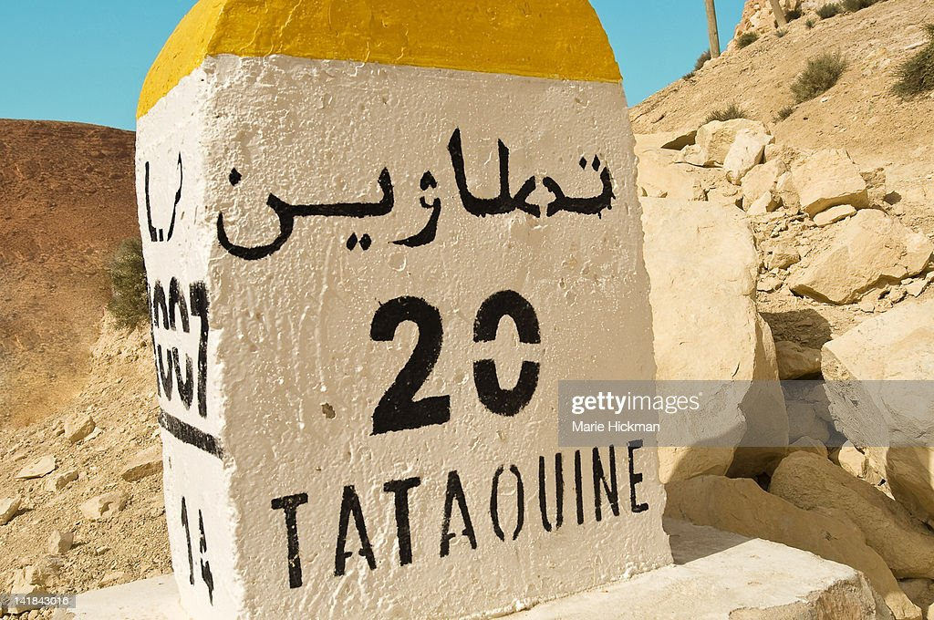 White milemarker (bourne) with yellow top, Tatouine written on mile marker with number 20 and arabic writing, Tataouine, Tunisia : Stock Photo