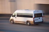 white minibus quickly goes on the highway