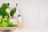 White modern kitchen decor with beige natural wooden dish, utensils, fresh green salad on wood background.