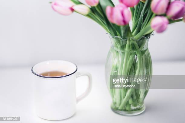 A white mug and a bouquet of tulips