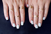 White nail art manicure, beauty hands with fashion gold rings. Trendy accessories top view