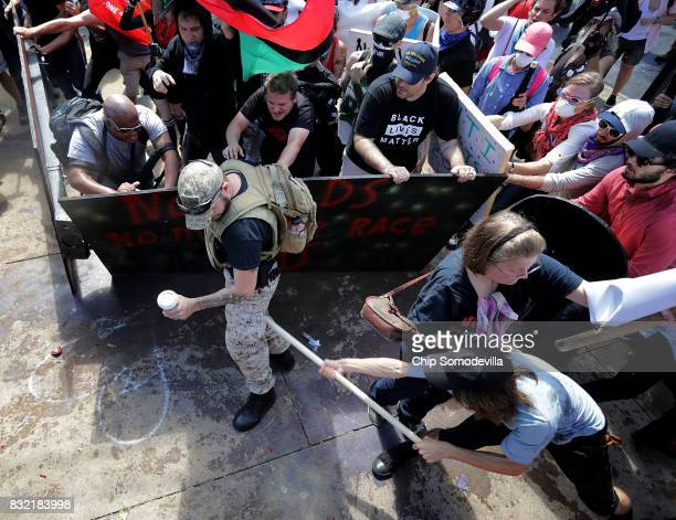 A white nationalists attempts not to spill his drink while clashing with counter protesters on the outskirts of Emancipation Park during the Unite...