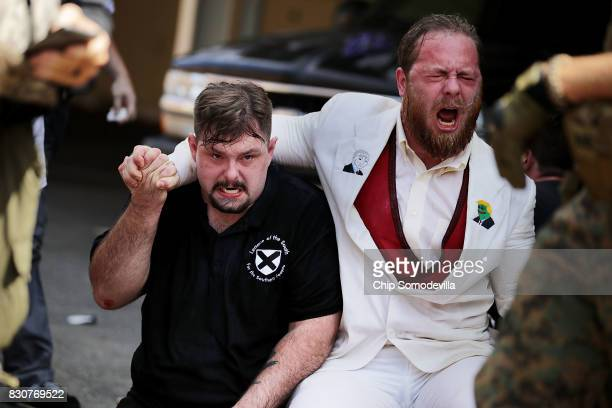 White nationalists neoNazis and members of the 'altright' take refuge in an alleyway after being hit with pepper spray after the 'Unite the Right'...