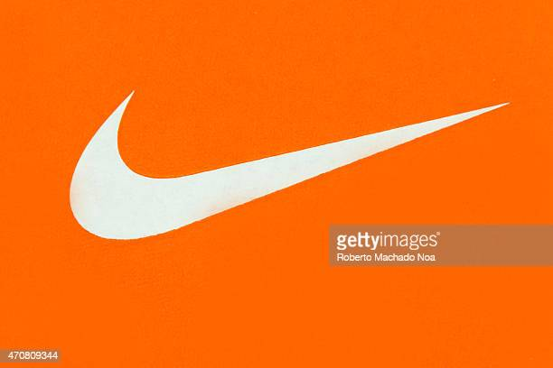 White Nike Logo on Orange BackgroundNike Inc is an American multinational corporation that is engaged in the design development manufacturing and...