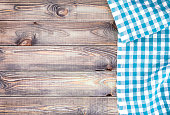 White old wooden table with blue checkered tablecloth, top view with copy space