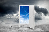 white open door on abstract grey concrete floor in front of blue cloudy sky change concept background