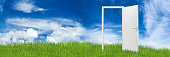 white open door on green grass landscape in front of blue cloudy sky change wide panorama concept background