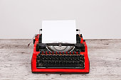 Photo vintage red typewriter on the table with paper