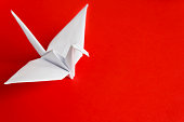 A white paper bird on a red background