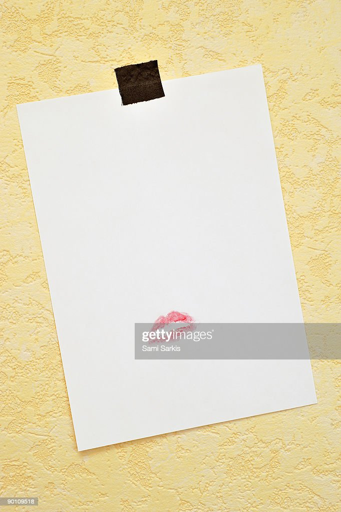 White paper hanged on wall with lipstick kiss : Stock Photo