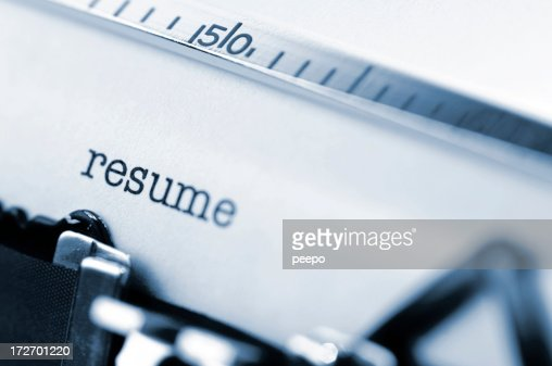 White paper in a typewriter with the word resume typed.
