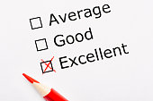 White paper sheet with checkboxes and red pencil. Survey asks the persons opinion whether it is average, good or excellent. Customer satisfaction.