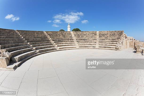 white Paphos lighthouse behind amphitheater against blue sky Cyprus