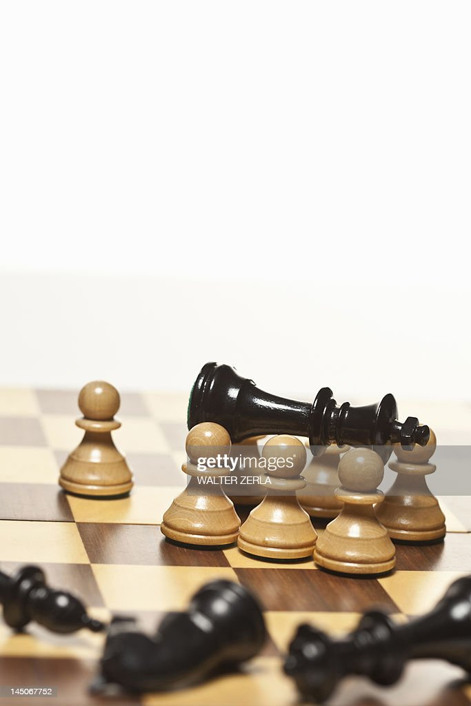 White pawns surrounding black chess king : Stock Photo
