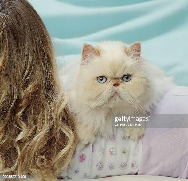 White Persian cat lying across girl's (5-7) back, close-up