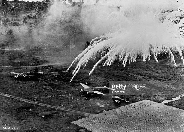 White phosphorus incendiary bombs burst over Japanese planes parked on an airfield at Rabaul on New Britain Island during an attack by American...