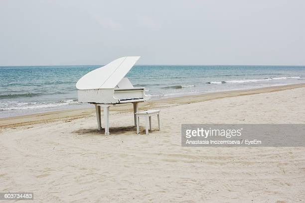 White Piano And Stool On Sandy Beach Against Clear Sky