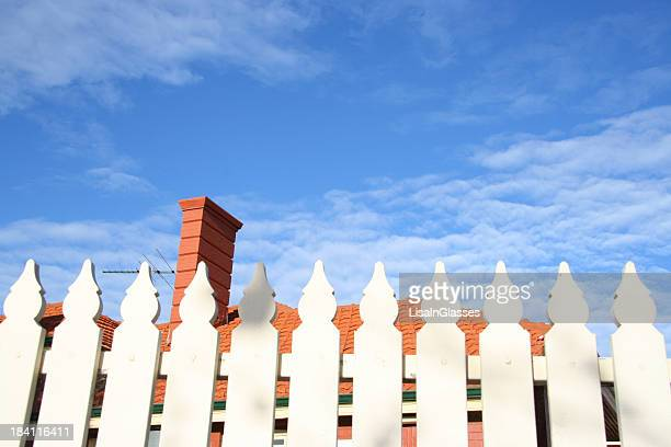 A white picket fence with a blue sky in the background