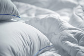 White pillows and blanket. Wrinkle messy blanket  in bedroom after waking up in the morning. Bed details. Duvet and blanket, an unmade bed in hotel bedroom with white blanket. Messy White Bed.