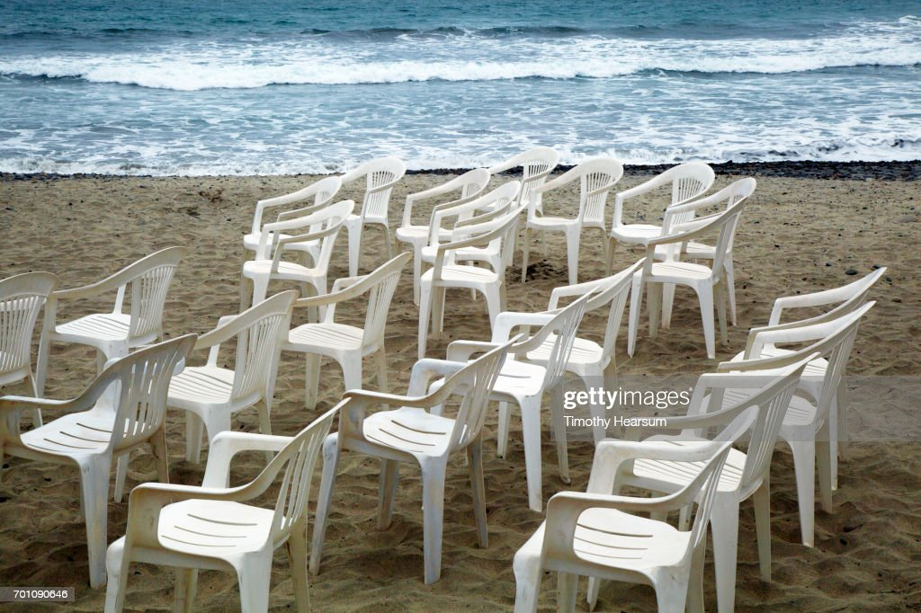 White plastic chairs on a beach; ocean beyond : Stock Photo