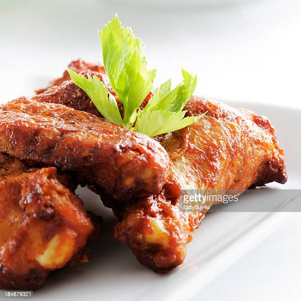 A white plate full of spicy chicken wings